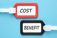 Benefit and Cost written on luggage tags. BENEFIT  and COST written on luggage tags on blue background. Benefit-Cost Analysis. Business concept Royalty Free Stock Photography