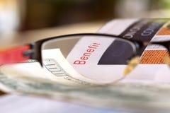 Benefit. Headlines through reading glasses Stock Photo