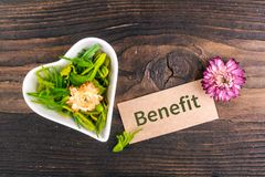 Benefit word on card. With dried flower and heart shape bowl on wood Stock Photo