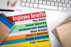 benefits anställd Kontorsskrivbord med ett datortangentbord och färgsidor Arkivbild