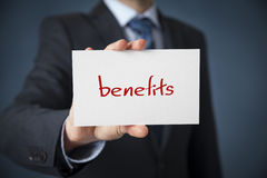 Benefits. Businessman show on card text benefits stock photography