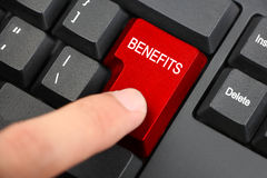 Benefits concept. Index finger pressing button of Benefits on black keyboard stock photo