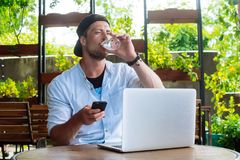 Benefits by drinking water. Man drink water while working at laptop, smartphone
