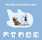 Benefits of flights in business class. Respectable businessman sitting in airplane seat, the stewardess bringing him a Royalty Free Stock Photography