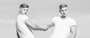 Benefits of having twin brother. Friendship and support. Men muscular twins brothers in white shirts sky background. Brotherhood concept. Benefits and stock photography