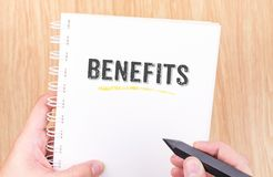 Benefits word on white ring binder notebook with hand holding pe Royalty Free Stock Images