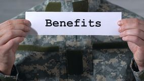 Benefits written on paper in soldier hands, financial assistance to veterans. Stock footage stock footage