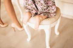 Benen av ett barn, lite flicka i en stol framme av en mirr Royaltyfri Fotografi