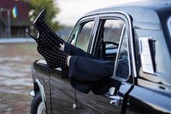 Benen av flickan i kängor med häl synliga i fönstret av bilen arkivfoton
