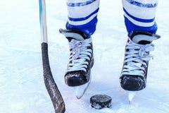 Benen av hockeyspelaren, pinnen och packningsnärbilden arkivbild