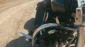 Benen av ryttaren är säkra på ställningarna av motorcykeln, som han springer ner vägen Motor- och pedalsikt lager videofilmer