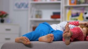 Benen die van jongen en meisje die op bank liggen, na actieve vrije tijd, dagslaap rusten stock footage