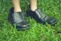 Benen die van leuk meisje zwarte bedrijfsschoenen dragen en zich op groen gras bevinden stock afbeeldingen