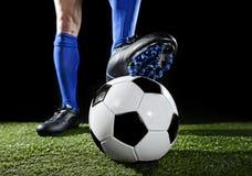 Benen en voeten van voetbalster in blauwe sokken en zwarte schoenen die met de bal het spelen op groen gras stellen royalty-vrije stock afbeelding