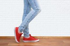 Benen in jeans en tennisschoenen stock foto's