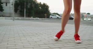 Benen in rode tennisschoenenstappen op bestrating stock video