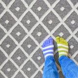 Benen in slecht gecombineerde sokken op grijs tapijt royalty-vrije stock fotografie