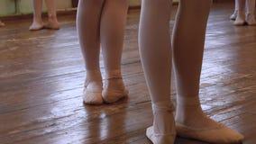 Benen van balerinas die zich in derde position do steps bevinden, ophouden en zich opnieuw in derde positie bevinden stock videobeelden