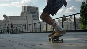 Benen van de jonge mens die skateboarder skateboardtruc in dag in de zomer, sportconcept, stedelijk concept, achtermening doen stock footage