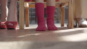 Benen van de moeder, weinig dochter en grootmoeder De vrouw heeft rode schoenen, meisjeskousen en oma beige sandals stock videobeelden