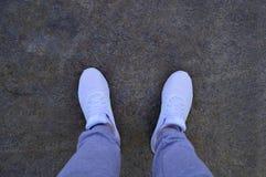 Benen van een kerel in witte tennisschoenen die zich op een steen bevinden royalty-vrije stock afbeeldingen