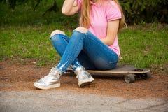 Benen van een meisje dat op een skateboard zit Stock Afbeeldingen