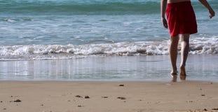 Benen van een tiener die aan het zeewater lopen royalty-vrije stock afbeelding