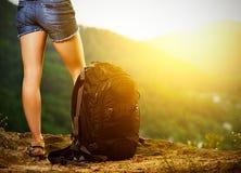 Benen van een vrouwentoerist en een reisrugzak op een bergbovenkant