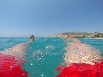 Benen van een zwemmer in het rode swimwear drijven in het overzees Royalty-vrije Stock Fotografie