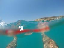 Benen van een zwemmer in het rode swimwear drijven in het overzees Stock Foto