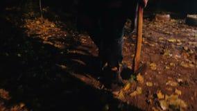 Benen van gevaarlijke seriemoordenaar die in duisternis, maniak lopen die scherpe bijl dragen stock footage