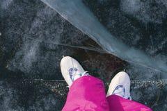 Benen van het meisje in vleten en roze de winter warme broek op het mooie ijs van Meer Baikal met barsten en sneeuw in de winter royalty-vrije stock foto's