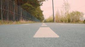 Benen van het voet lopen langs asfaltweg voorbij omheining in park op de herfstdag stock videobeelden