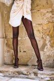 Benen van het zwarte Afrikaanse model stellen in de straat tegen een muur stock afbeelding