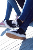 Benen van jong meisje in jeans en tennisschoenen Royalty-vrije Stock Foto