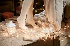 Benen van jong paar in donker binnenland met lichten, kaarslantaarn De vakantie van het nieuwjaar Kerstmislichten en decoratie Ge Stock Afbeeldingen