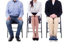 Benen van jonge bedrijfsmensen die op geïsoleerde bureaustoelen zitten royalty-vrije stock fotografie