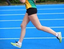 Benen van jonge vrouwelijke atletenlooppas in atletiekspoor Royalty-vrije Stock Afbeeldingen