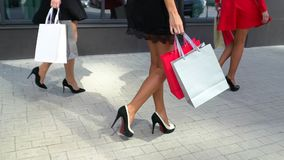 Benen van shopaholics met het winkelen zakken die onderaan wandelgalerij lopen Mooie vrouwelijke benen close-up van vrouwelijke b stock video