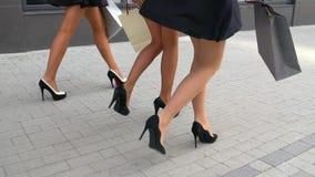 Benen van shopaholics met het winkelen zakken die onderaan wandelgalerij lopen Mooie vrouwelijke benen close-up van vrouwelijke b stock videobeelden