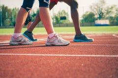 Benen van twee atleten in tennisschoenen stock foto's