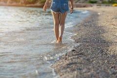 Benen van vrouwen die op het strand bij zonsondergang lopen Royalty-vrije Stock Fotografie