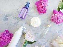 Benessere cosmetico crema di trattamento di estate della decorazione della lozione della peonia del fiore su calcestruzzo grigio immagini stock libere da diritti