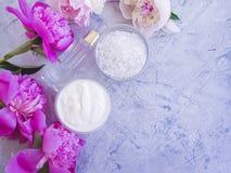 Benessere cosmetico crema di trattamento di estate della peonia del fiore su calcestruzzo grigio fotografia stock