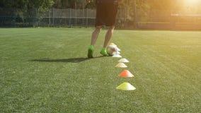 Benexpertisutbildning på fotbollfält Spring för fotbollspelare i ledande boll för fotbollfält mellan kottar arkivfilmer