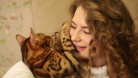 Bengal cat biting his mistress.