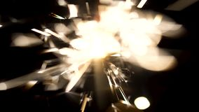Bengal fire with beautiful sparkles isolated on black background. Media. Burning sparkler in the dark, Merry Christmas stock footage