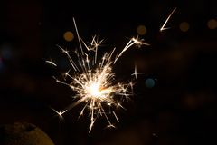 Bengal fire sparkles against the background of city lights, blurred bokeh. royalty free stock photo