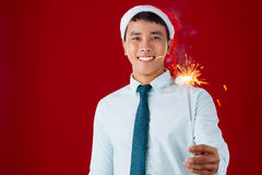 Bengal light. Young businessman in Santa hat holding a Bengal light Stock Image