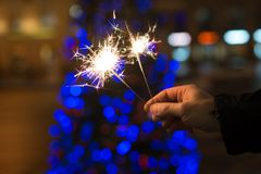 Bengal lights, sparkle on blue lights for tree background. Christmas time, New Year Royalty Free Stock Photos